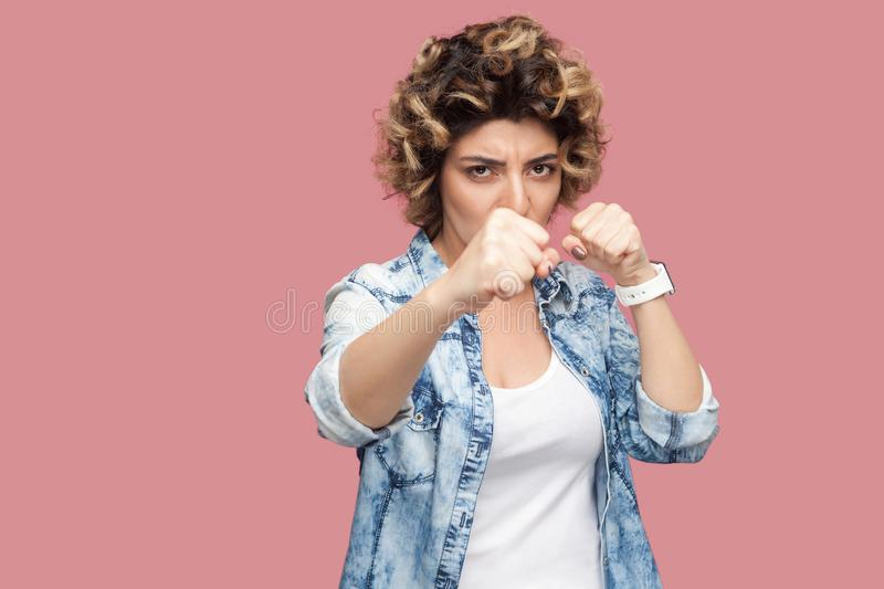 Portrait of serious young woman with curly hairstyle in casual blue shirt standing with boxing fists, looking at camera and ready. To attack. indoor studio shot royalty free stock image