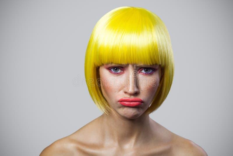 Portrait seulement de jeune femme mignonne malheureuse avec des taches de rousseur, maquillage rouge et perruque jaune, regardant photo stock