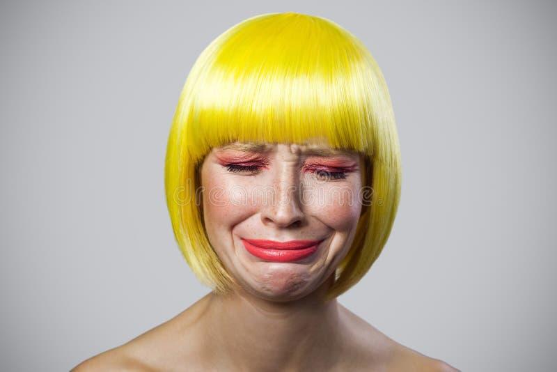 Portrait seulement de jeune femme mignonne triste avec des taches de rousseur, maquillage rouge et perruque jaune, pleurant et dé photos stock