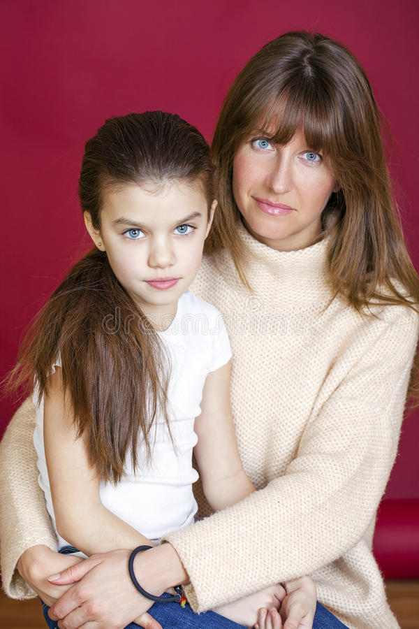 Portrait of seven year old daughter and young mother stock images