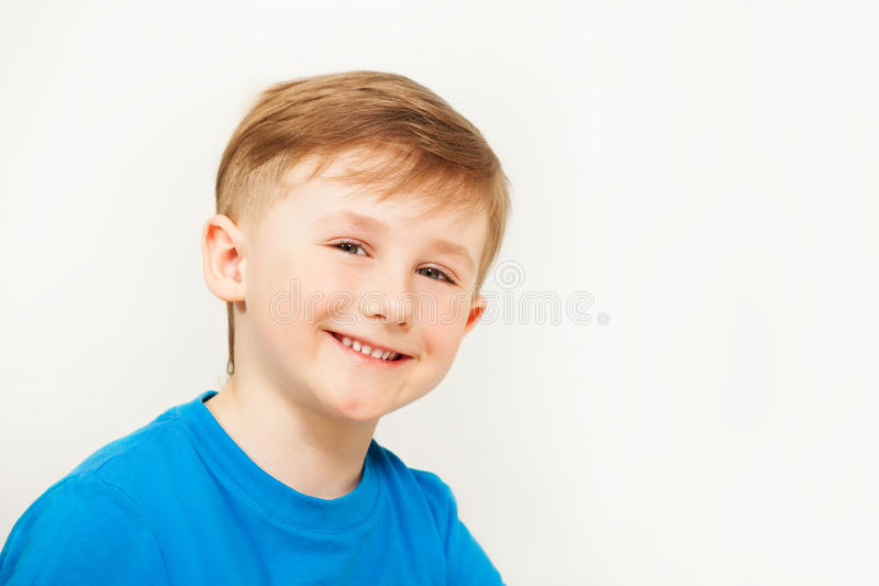 Portrait of seven years old boy in blue t-shirt. Close-up portrait of cheerful seven years old boy in blue t-shirt posing against blanked background royalty free stock images
