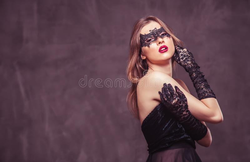 Woman in Black Mask. Portrait of attractive brunette woman wears black mask on grey studio background with copyspace royalty free stock image