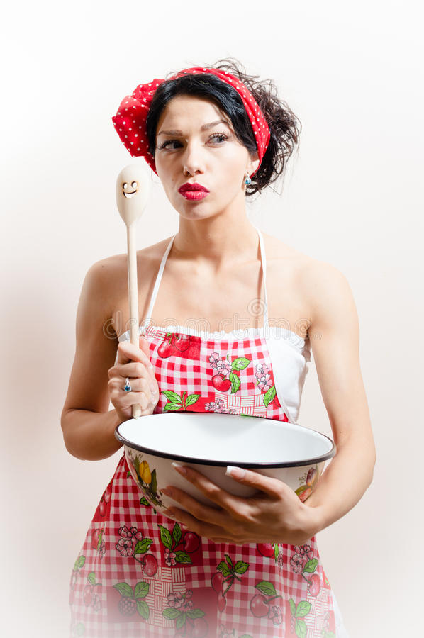 Portrait of attractive pinup girl holding bowl and spoon & looking at camera curious on white or light copy space royalty free stock image