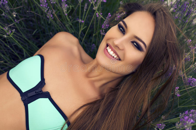 Portrait of beautiful girl in bikini posing at lavender field royalty free stock images