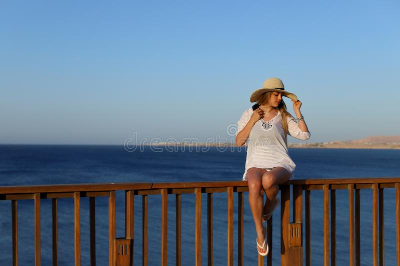 Portrait of a Sexy beautiful tanned woman relaxing in swimsuit and with light beach dress on terrace with blue sea and stock images