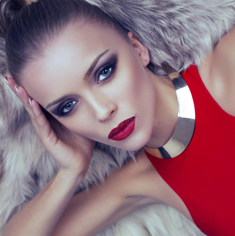 Portrait of blond woman in red dress with fur coat. Fashion photo of beautiful woman with blond hair in red dress with fur coat royalty free stock image