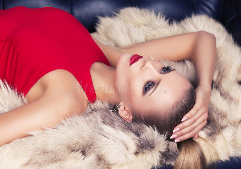 Portrait of blond woman in red dress with fur coat. Fashion photo of beautiful woman with blond hair in red dress with fur coat royalty free stock photos