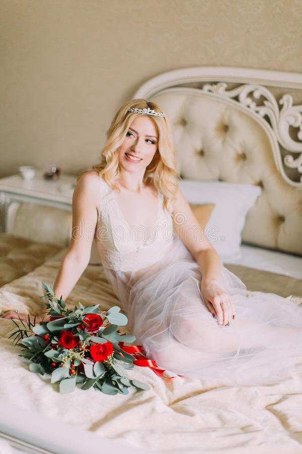 Portrait of blonde bride in white underwear sitting on bed. Bouquet with red roses royalty free stock photos