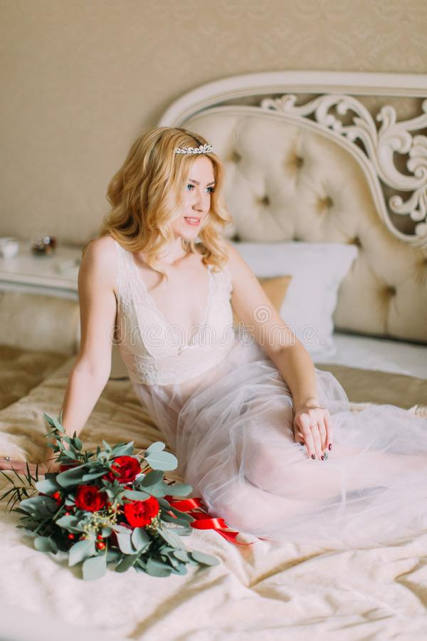 Portrait of blonde bride in white underwear sitting on bed. Bouquet with red roses stock photo