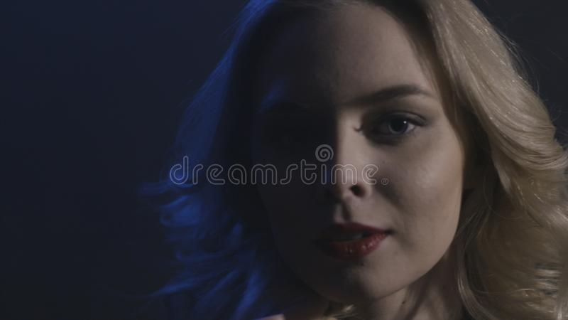 Portrait of sexy blonde woman with curly hair and red lips looking straight isolated on black background. Action. Close. Portrait of sexy blonde woman with curly royalty free stock images
