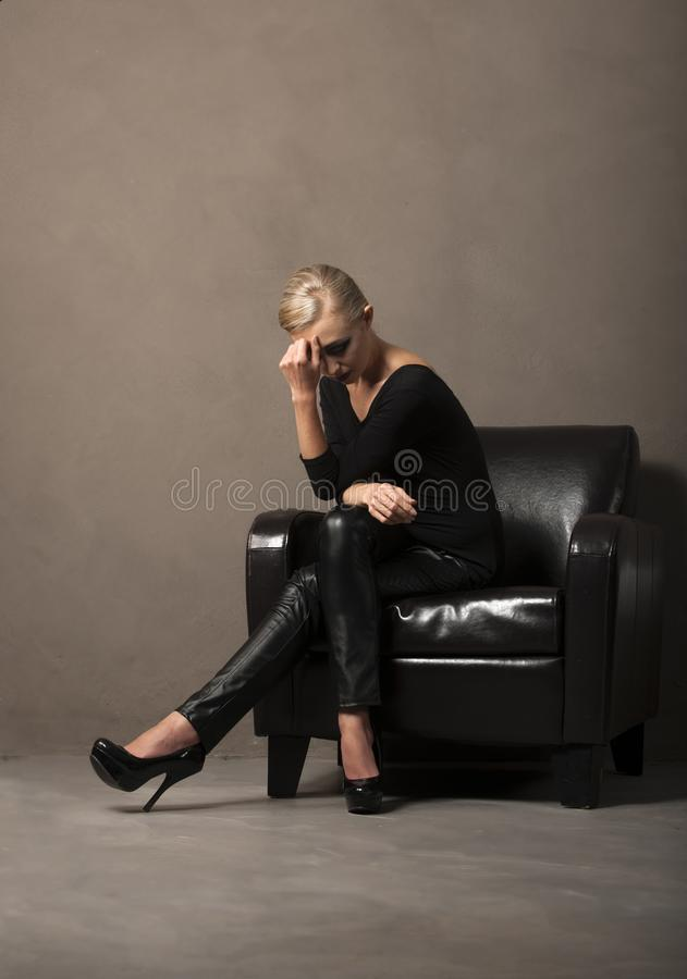Portrait of blonde woman seated in chair royalty free stock image