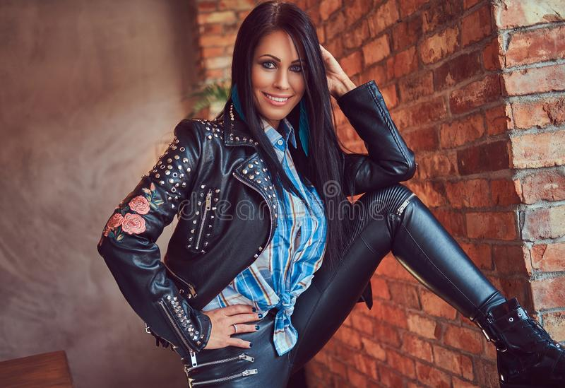 Portrait of a brunette in leather jeans and jacket posing against a brick wall in a room with a loft interior. stock photography