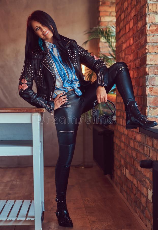 Portrait of a charming brunette posing in a stylish leather jacket and jeans while leaning foot on the window sill. royalty free stock images