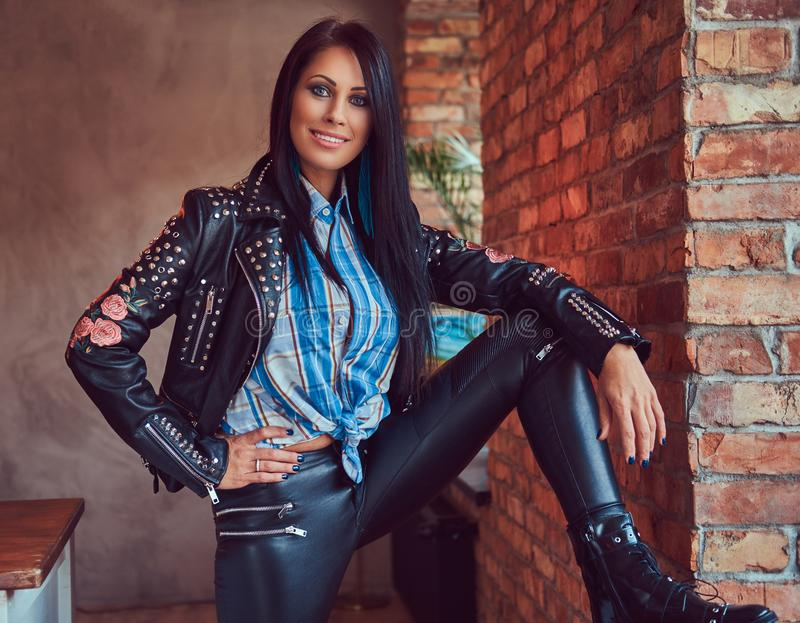 Portrait of a charming brunette posing in a stylish leather jacket and jeans while leaning foot on the window sill. stock photography