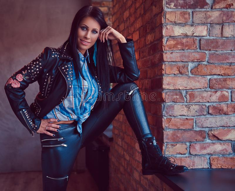 Portrait of a charming brunette posing in a stylish leather jacket and jeans while leaning foot on the window sill. stock images