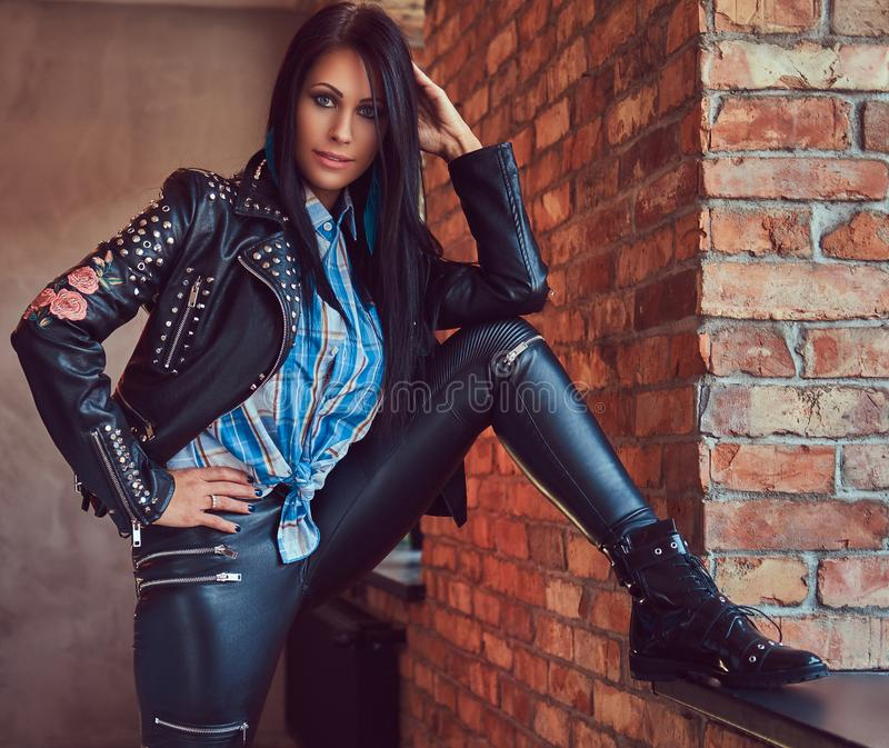 Portrait of a charming brunette posing in a stylish leather jacket and jeans while leaning foot on the window sill. royalty free stock image
