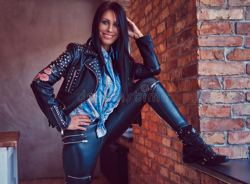 Portrait of a charming brunette posing in a stylish leather jacket and jeans while leaning foot on the window sill. stock photos