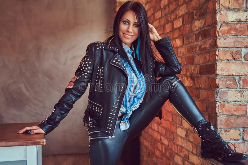 Portrait of a charming brunette posing in a stylish leather jacket and jeans while leaning foot on the window sill. royalty free stock photo