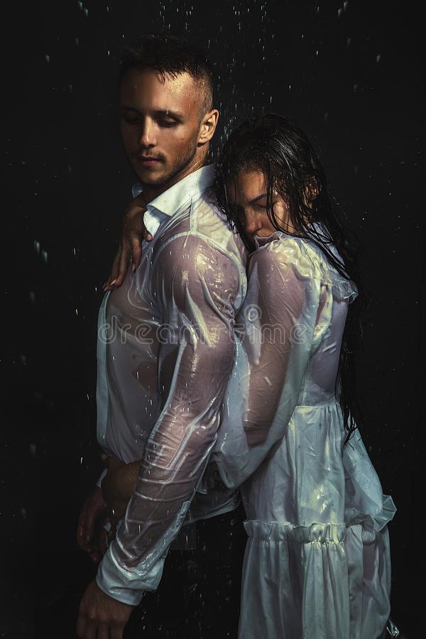 Portrait of couple in white shirt and dress standing under rain stock photography