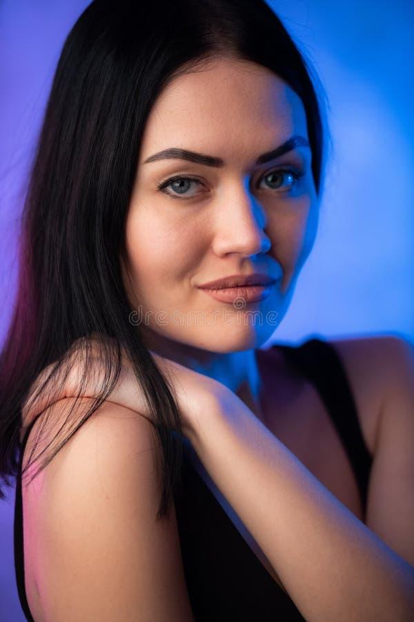 Portrait sexy de jeune femme, sur le fond color? Fille mod?le de brune s?duisante dans des v?tements sexy noirs, maquillage lumin photographie stock