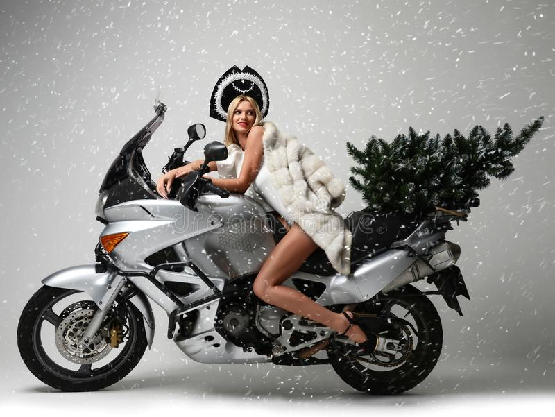 Portrait of fashion blonde woman in Christmas tree sitting ride motorcycle. Portrait of fashion blonde woman with Christmas tree sitting riding motorcycle royalty free stock photography