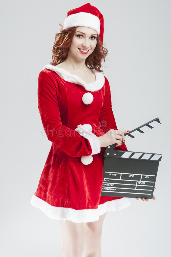 Portrait Of female Santa Girl with Clapperboard Posing Agai. Nst White Background. Vertical Image Composition royalty free stock images