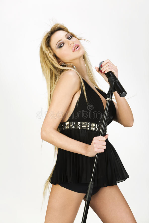 Portrait of a female singer. With microphone in hand stock photos