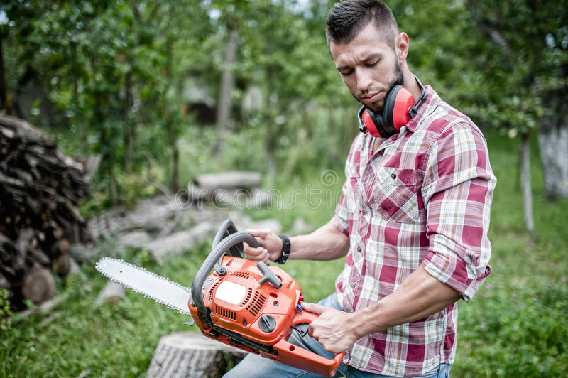 Portrait of and hansome man with chainsaw. And protective gear ready for cutting wood stock photos