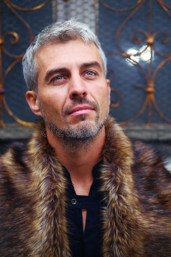 Portrait of a man in wolf fur and ornamental medieval window on background stock photo
