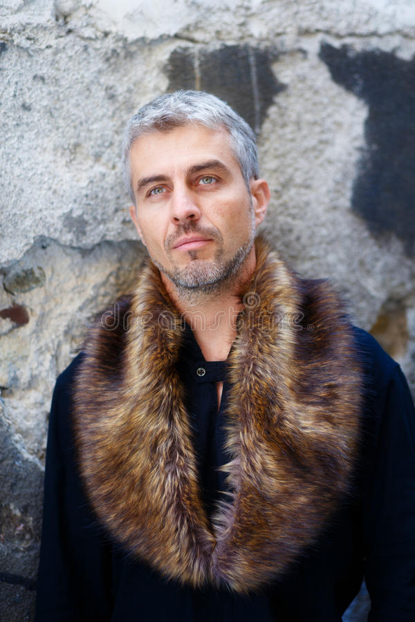 Portrait of a man in wolf fur and thoughtful expression on his face, a structure wall on background stock images