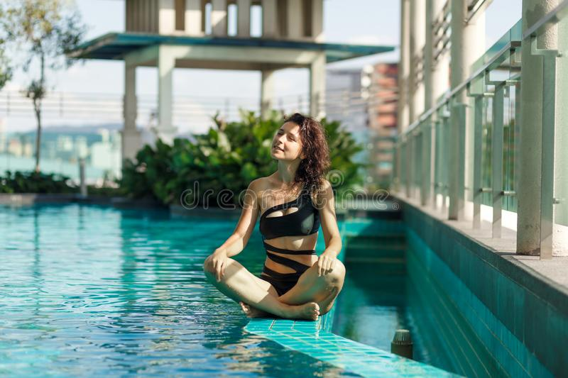 Portrait of a sexy meditation caucasian woman in a swimsuit sitting in lotus pose on the edge of a rooftop pool with green bushes royalty free stock photos