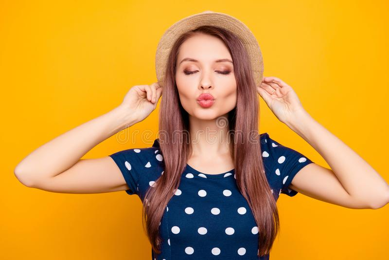 Portrait of sexy, nice, lovely, pretty, adorable woman in polka-dot outfit holding hands on hat with close eyes, blowing air kiss. At camera with pout lips stock photos