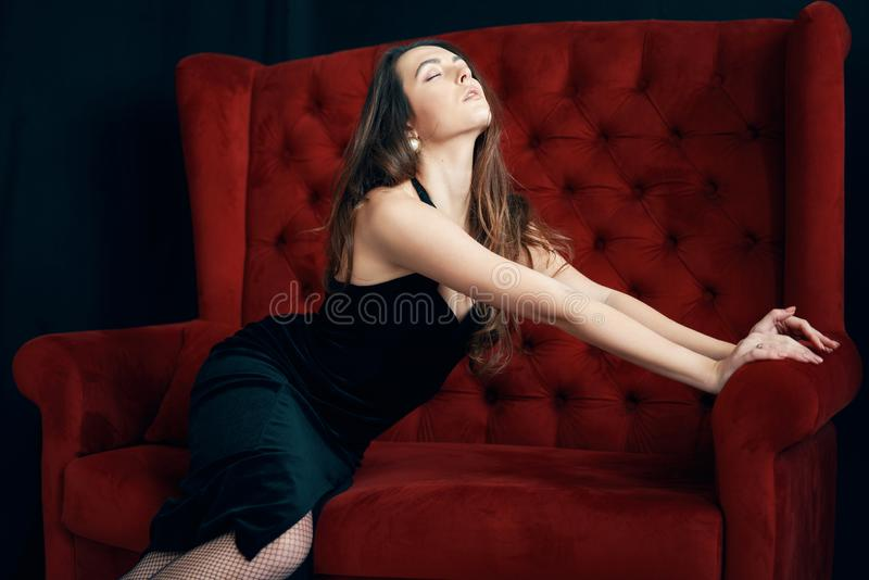 Portrait of sexy sensual woman in black dress posing on red sofa. Fashion concept royalty free stock photos