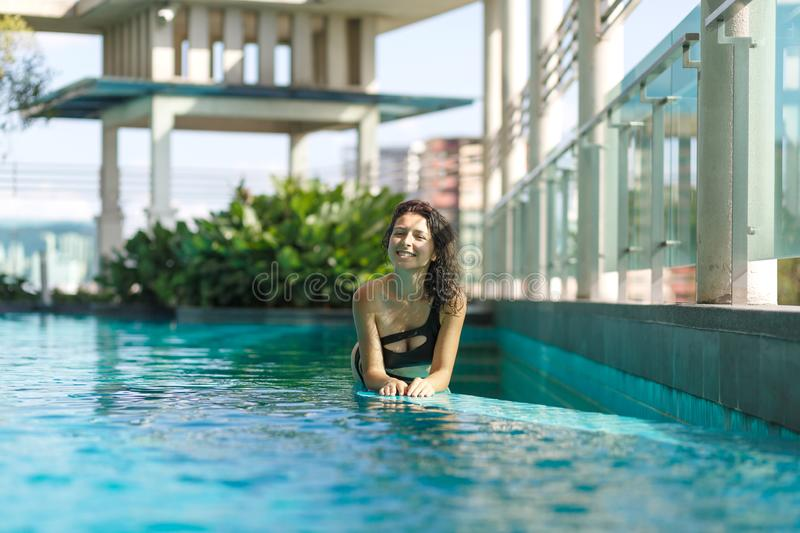 Portrait of a sexy smiling caucasian woman in a swimsuit lay on the edge of a rooftop pool with green bushes and city views. Asia royalty free stock photography