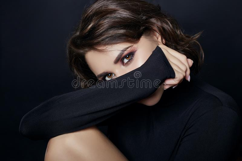 Portrait of woman with black turtleneck sweater with a long. Collar on a gray background closeup. Beautiful curly hair girl, big beautiful eyes and gorgeous royalty free stock photo