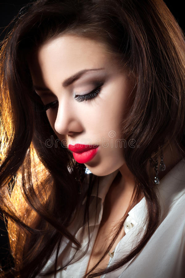 Portrait Of Woman On a dark metallic Background. Sensual brunette woman posing, looking at camera.Long curly healthy hair on a metallic background stock image