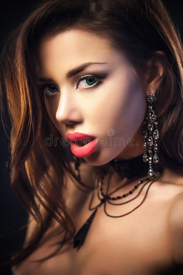 Portrait Of Woman On a dark metallic Background. Sensual brunette woman posing, looking at camera.Long curly healthy hair on a metallic background stock photography