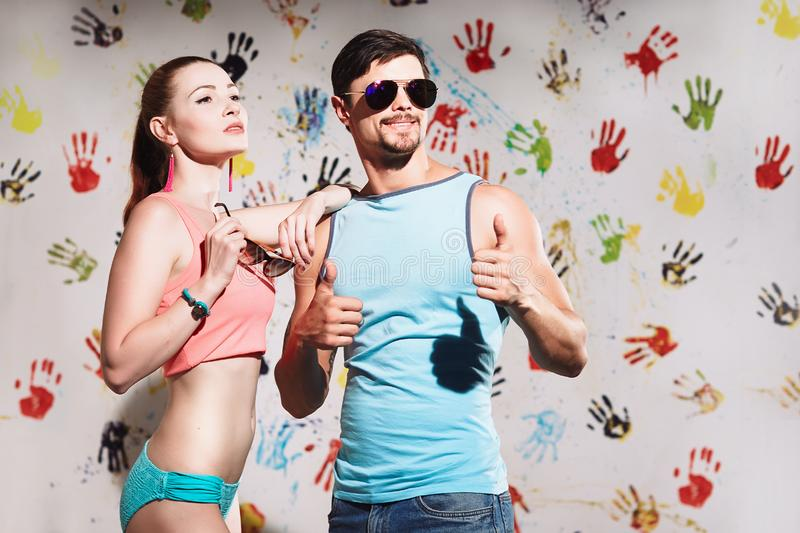 Portrait of young couple with thumbs up sign on a funny pos stock photo