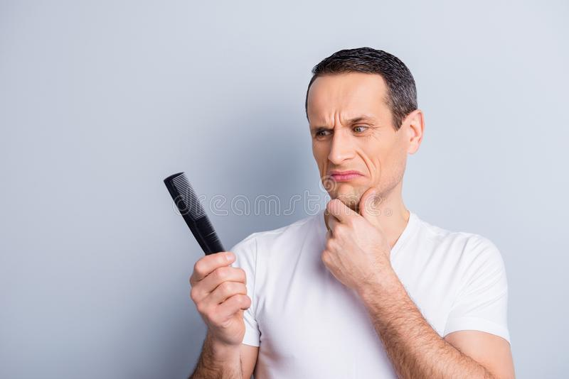 Portrait of shaved, trendy, experienced, brunet, neat man touching his chin with hand looking at comb in his hand with disgust ex stock image