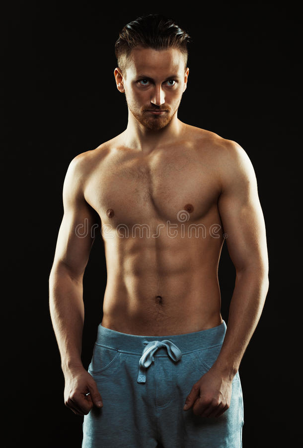 Portrait of a shirtless confident young athletic man standing ag stock image