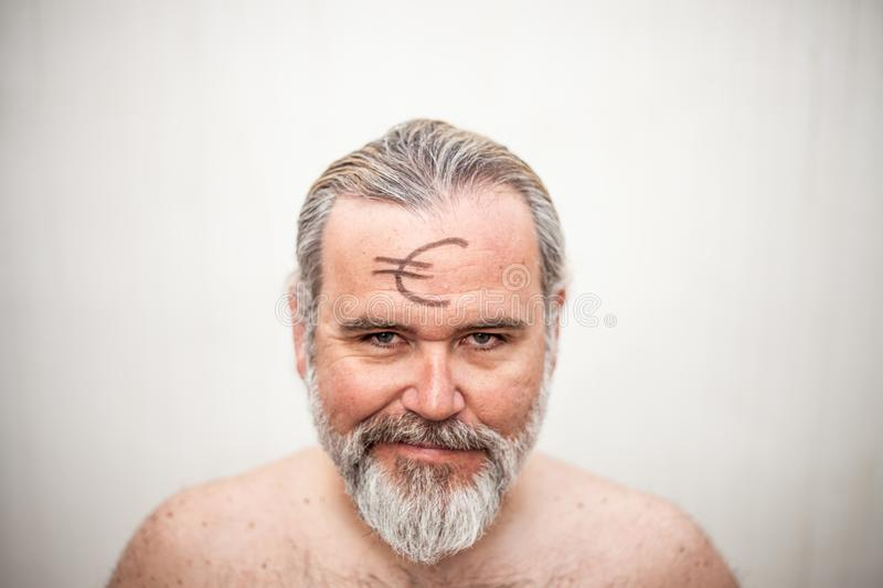 Portrait of a shirtless man with the euro icon drawn on the forehead royalty free stock photos