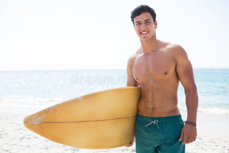Portrait of shirtless muscular man holding surfboard at beach stock images