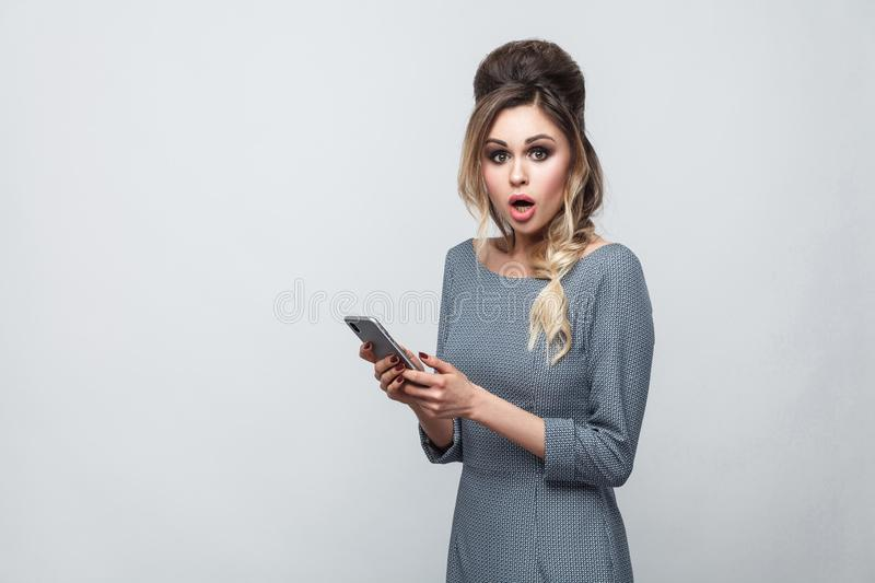 Portrait of shocked beautiful blogger teenager wearing in grey dress with pigtail on head standing, using smartphone and watching. Video with amazed face royalty free stock photography