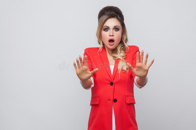Portrait of shocked beautiful business lady with hairstyle and makeup in red fancy blazer, standing with blocking hands and. Looking at camera. indoor studio royalty free stock image