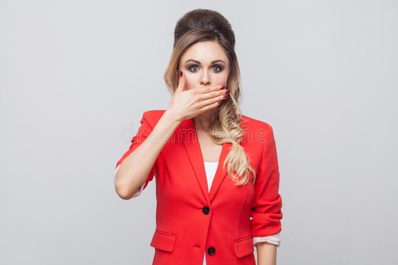 Portrait of shocked beautiful business lady with hairstyle and makeup in red fancy blazer, standing and covering her mouth and. Looking at camera with big eyes royalty free stock image