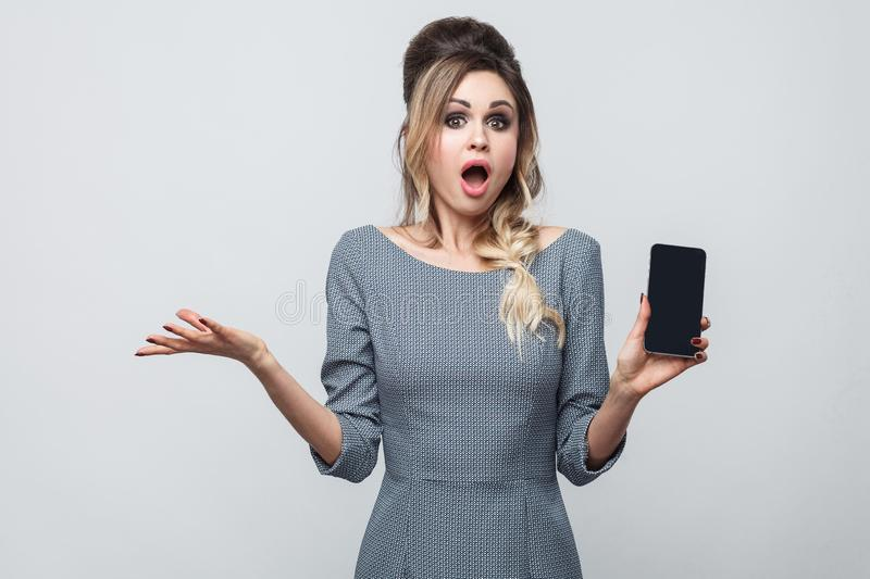 Portrait of shocked beautiful modern young girl in grey dress standing, holding and pointing finger to cell phone and amazed face royalty free stock photos