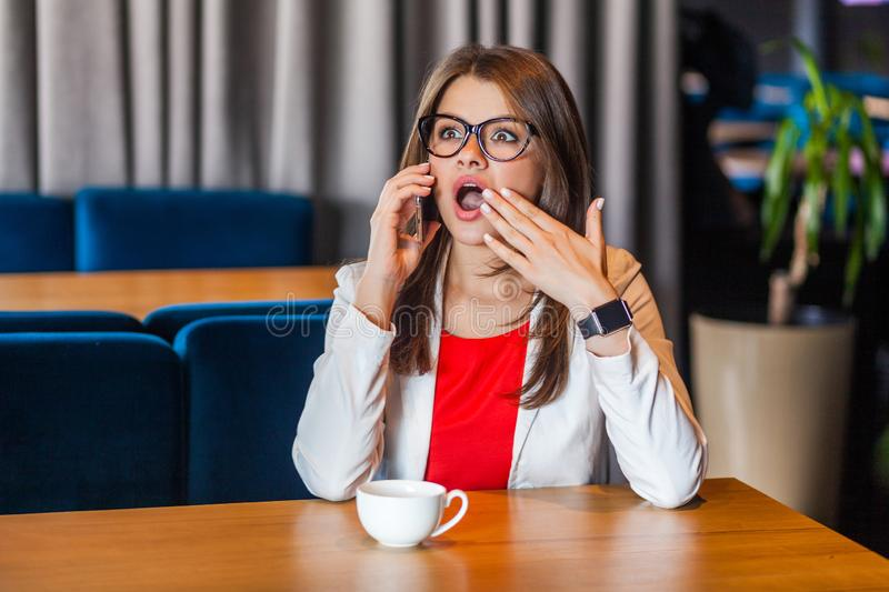 Portrait of shocked beautiful stylish brunette young woman in glasses sitting listeting amazed news on her mobile smart phone and stock photography
