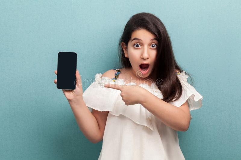 Portrait of shocked beautiful teenager girl in white dress standing, holding phone and pointing finger at display with opened. Mouth, looking at camera. Indoor stock photography