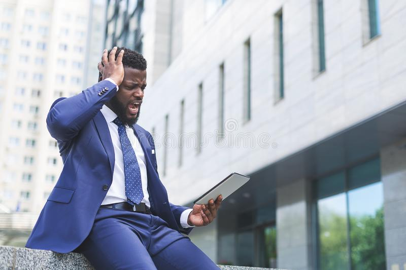 Portrait of shocked businessman looking at tablet while sitting in an urban setting stock photos