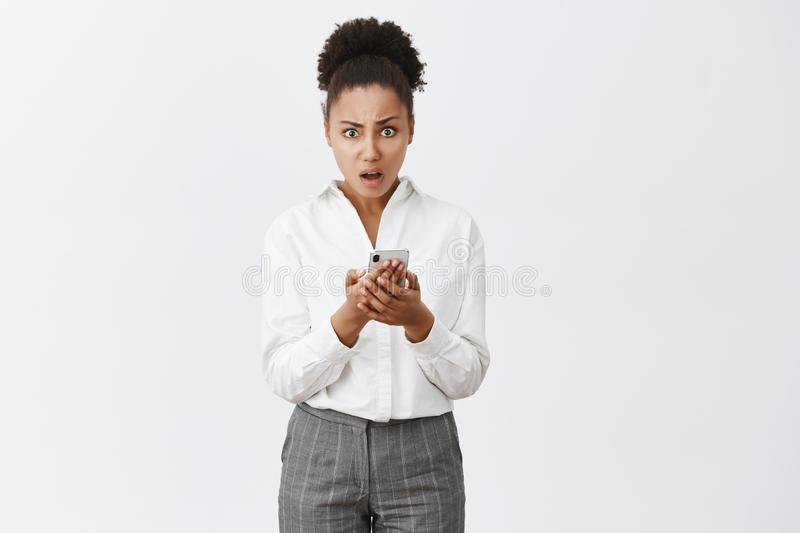 Portrait of shocked confused and displeased good-looking african-american woman in suit, holding smartphone and staring. Puzzled at camera, being disappointed stock photo
